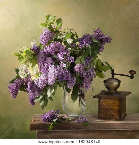 Still life A bouquet of lilac in a glass jug on a wooden table with a picturesque background and an old coffee grinder