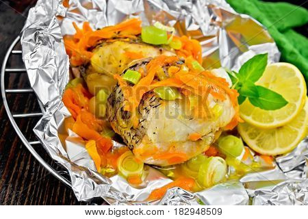 Pike With Carrots And Basil In Foil On Dark Board
