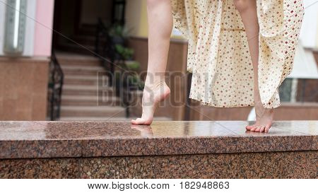 Sexy legs of young dancing girl on a marble parapet. Close up.