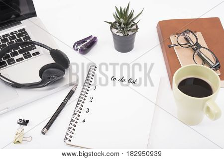 computer headset and coffee cup with to do list on desk from above planning and schedule concept.