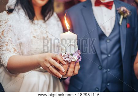 the bride and groom holding a candle during a wedding ceremony in the restaurant