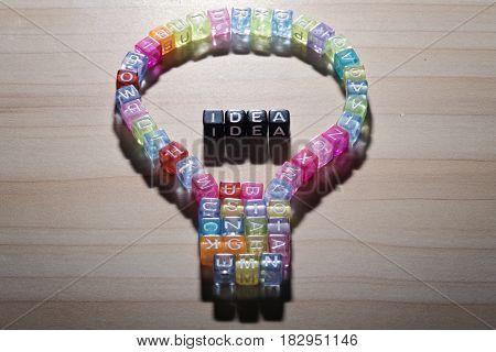 IDEA inside LIGHT BULB, by colorful alphabet beads