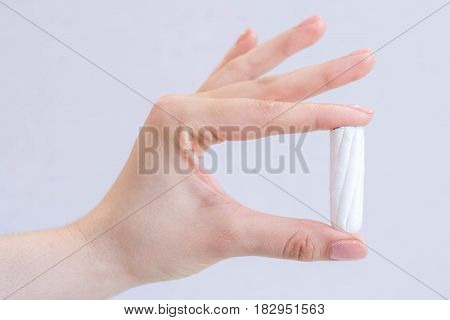 Woman's hand holding clean cotton tampon close-up. Young woman preparing menstruation time. Soft tender protection woman critical days, gynecological. Medical hygiene conception