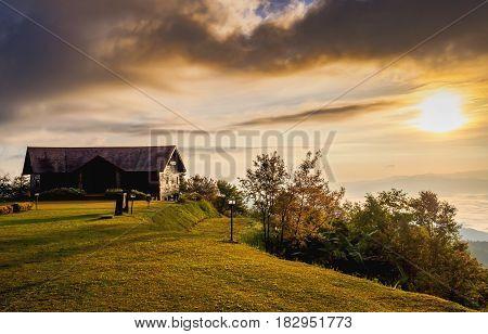 Sunrise beyond wooden hut in mountain terrain.