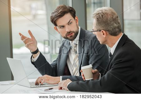 Stylish adult businessmen while working day in office. Businessmen working with laptop. Office interior with big window