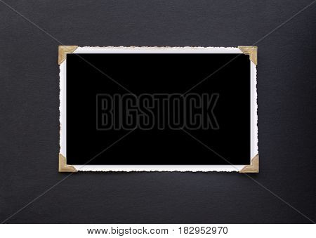 Photo frame - real old photo with black blank space for copy photo or text pasted with gold coloured photo holder corners onto black vintage album paper page