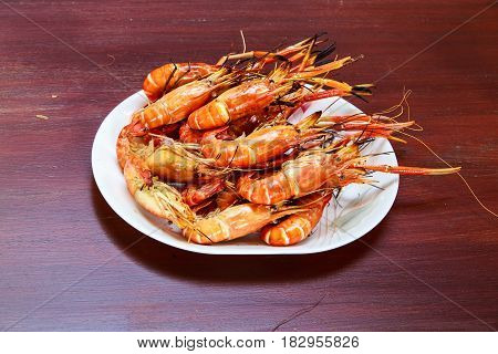 Hot BBQ Grilled river prawns in white plate, wooden background.