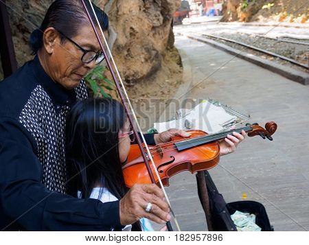 Kanchanaburi Thailand - December 252516 : Asian musician violinist teaching young girl playing violin in public park.