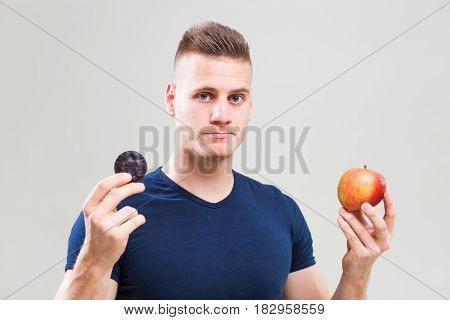 Studio shot image of young sporty man who is deciding whether to eat apple or candy.