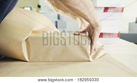 Close up man's hands packing boxes of sellotape in printing industry, Caucasian
