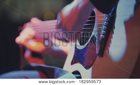 Guitarist in night club - musician plays blues acoustic guitar, extremely close up, telephoto