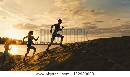 Sport motivations -group of athletes - two girls and a guy are fleeing the mountain, near river at dusk, silhouette