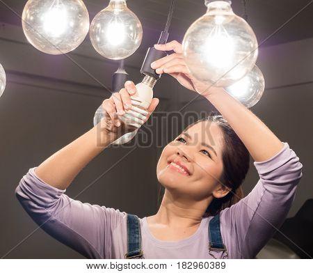 asian woman wearing jumpsuit changing light bulb