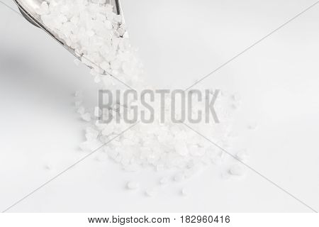 Sea salt in an iron bowl on a white background