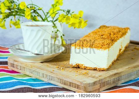 Professional bakery. White cheesecake with orange sweet crumbs. The vase with daisies and porcelain cup with hot tea