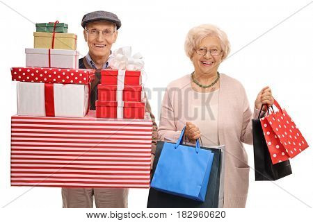Mature man with presents and a mature woman with shopping bags isolated on white background