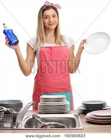Young woman with an apron holding a detergent and a clean plate isolated on white background