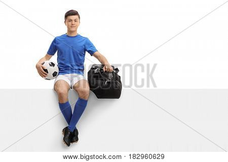 Teenage soccer player with a football and a bag sitting on a panel isolated on white background