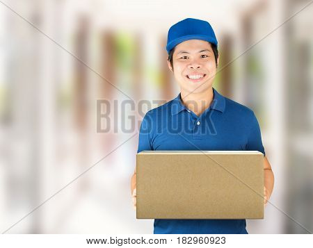 asian delivery man wearing blue shirt holding carton box
