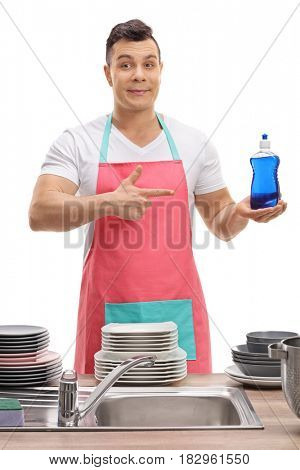 Young man behind a sink holding a detergent and pointing isolated on white background