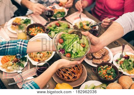 Family dinner. Beautiful family having meal. Tasty food on table. Happy family enjoying time together. Woman giving fresh salad