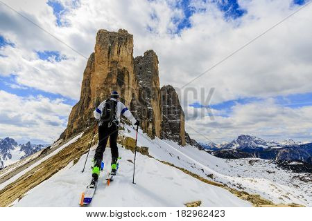 Mountaineer backcountry ski spring walking up along a snowy ridge with skis. In background blue cloudy sky and shiny sun and Tre Cime, Drei Zinnen in South Tirol, Dolomites, Italy.