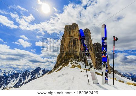 Mountaineer backcountry ski equipment in spring snow.  In background blue cloudy sky and shiny sun and Tre Cime, Drei Zinnen in South Tirol, Dolomites, Italy. Adventure winter extreme sport.