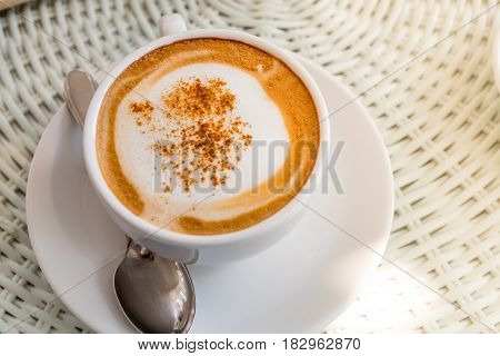 The coffee with spoon on the white table with the sun shine