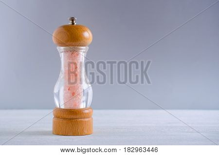 pink himalayan salt crystals in a glass wooden grinder on gray background