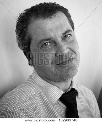 Monochrome portrait of middleaged man dressed in a shirt and tie