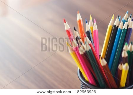 Set Of Colored Pencils In The Glass, Wooden Background