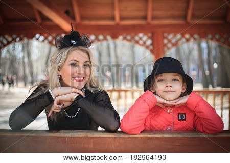Happy mother and daughter portrait in retro style outdoors on a sunny day.