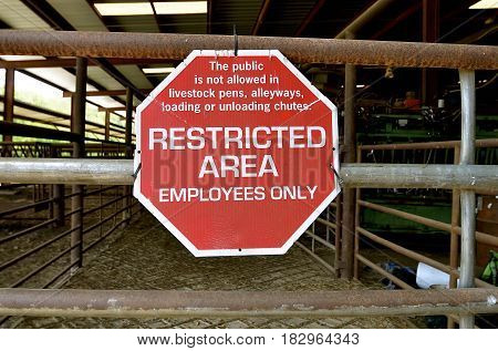 A livestock auction building sign allows for employees only as it is a restricted area.