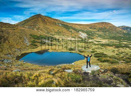 Tourist Standing On A Big Stone Near The Mountain Lake