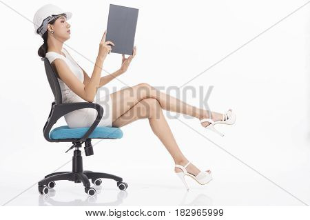 Sexy girl structural engineer looking at file on white background