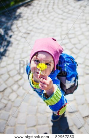 The Boy With The Backpack Shows A Dandelion Flower.