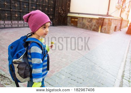A Boy With A Backpack Walking Across The Street.