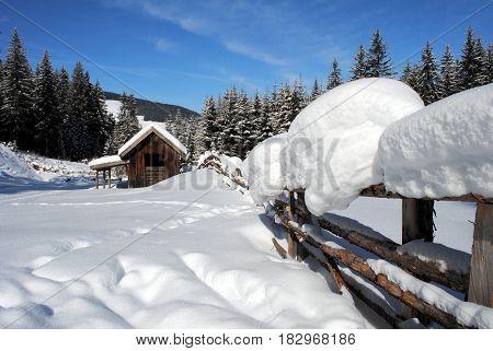houten omheining en houten hut in sneeuw landschap
