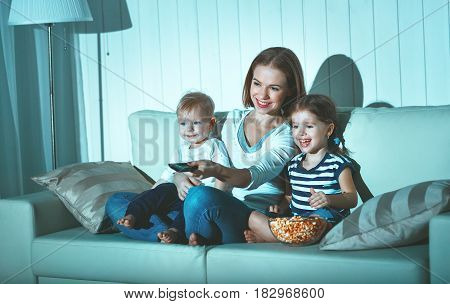 Family mother and children watching television at home on the sofa