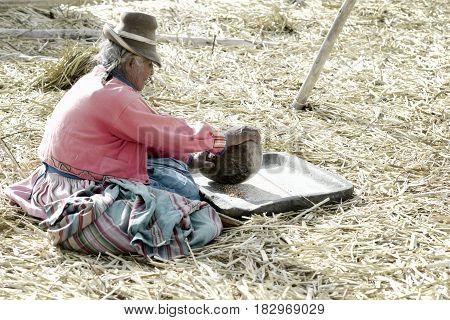 An elderly Aymara woman grinding corn. October 17, 2012 - The Uros Floating Islands, Lake Titicaca, Peru