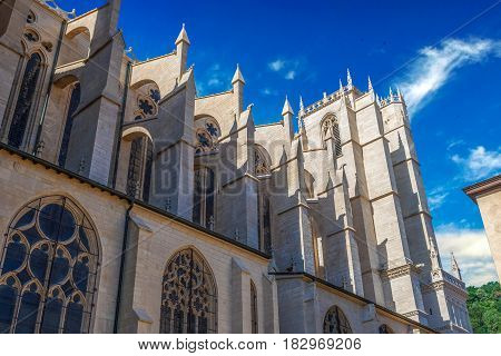 Side bottom view of Part of cathedral Saint Jean-Baptiste in Lyon, France. Summer day with clear blue sky and white clouds.