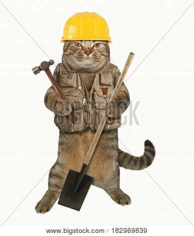 The cat builder is holding a hummer in one paw and a shovel in other. He is wearing a construction helmet and vest. White background.