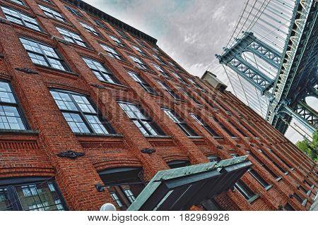 Tower of Manhattan Bridge and brick wall.