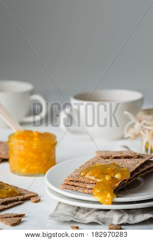 Brown Rye Crisp Bread (swedish Crackers) With Spread Orange Jam And Cups Of Tea, On White Background