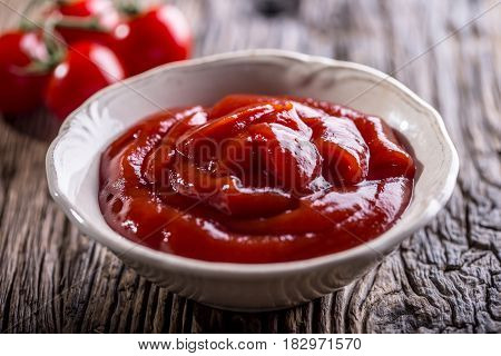 Ketchup or tomato sauce in white bowl and cherry tomatoes on wooden table.