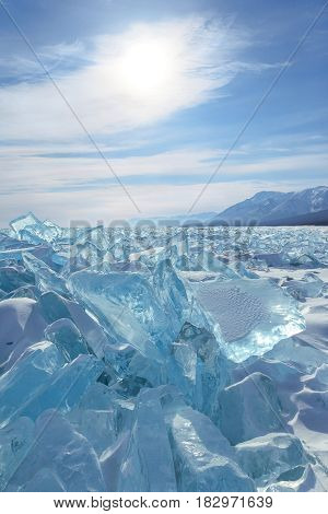Blocks of semitransparent blue ice on sky background