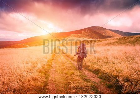 Hiker with bagpack walking the treck to the top of mountain