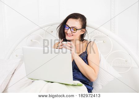 Sunday morning in bed. Middle aged woman surfing internet at her laptop computer. High key.