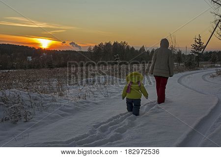 Mother and her little daughter walking through a snowy field. Мать и дочь идут на фоне заката.