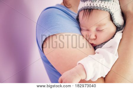 Cute newborn baby girl sleeping. Young woman holding infant child